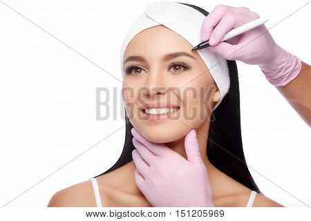 Young woman before plastic surgery operation. Beautiful woman ready for cosmetic surgery, female face with doctor's hands with pencil, over white. Woman face plastic operation. Aesthetic face