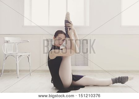 Classical Ballet dancer portrait. Beautiful graceful ballerine in black practice leg stretching in class room background. Ballet class training, high-key soft toning.