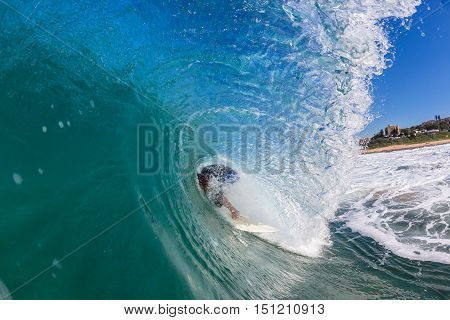Surfer surfing inside hollow tube barrel about to wipe out closeup water photo.