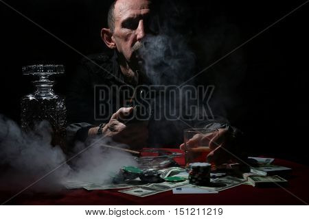old seriouse man smoke pipe and play poker