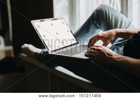 Cropped shot of a young male using his laptop while half-sitting on a windowsill.