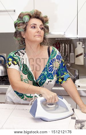 Beautiful Mature Woman With Curlers Ironing Clothes At Home