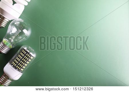 different lamp on green background concept savings