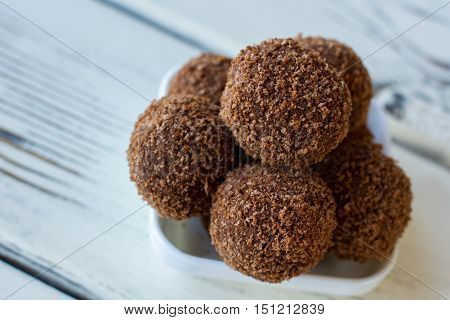 Candies covered in crumbs. Little brown desserts. Delicious chocolate rum balls. Recipe of dessert with alcohol.