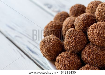 Pile of brown candies. Desserts with crumbs. Fresh and tasty chocolate balls. Biscuits and cocoa.