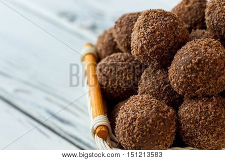Dark sweets with crumbs. Pile of candies in basket. Recipe of chocolate rum balls. Delicious russian dessert.