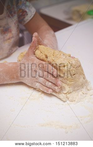 Vintage tonned photo with kid kneading the dough. Child helps to cook tasty cookies