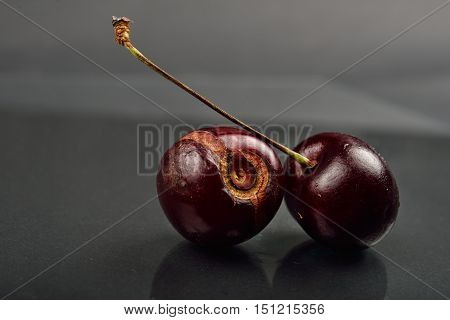 Close Up Of Image Of Rotten Red Cherries Fruit On Reflective Black Background. Selective Focus. Ligh