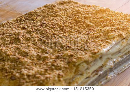 Big layered cake. Cream and crumbled biscuits. Freshly cooked millefeuille. Simple and tasty dessert.