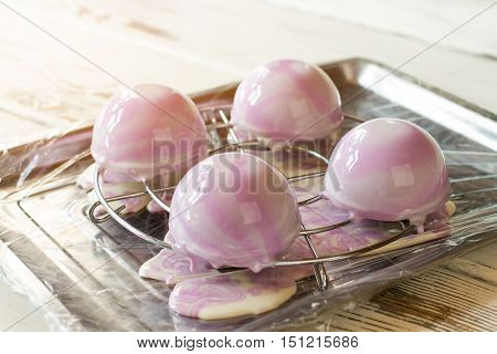 Desserts with liquid icing. Small half sphere cakes. Production of glazed sweets. Special order in pastry shop.