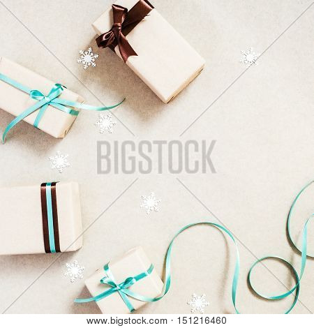 Christmas background with four gift boxes wrapped in kraft paper and paper snowflakes. Close up.