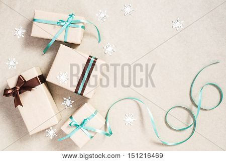 Christmas background with four gift boxes wrapped in kraft paper and paper snowflakes