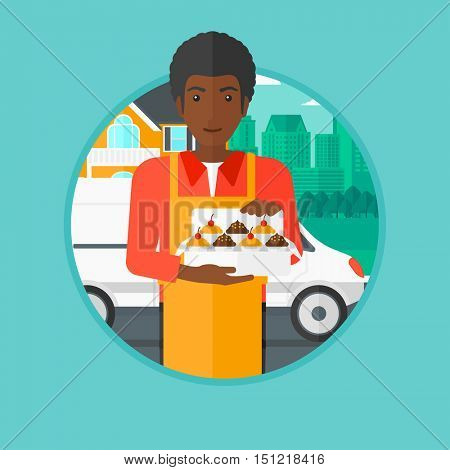 An african-american male baker holding a box of cupcakes on the background of delivery truck. Young baker delivering cakes. Vector flat design illustration in the circle isolated on background.