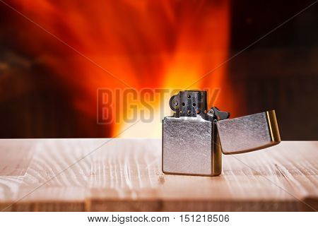 Cigarette lighter on natural wooden table in front of a fire place.