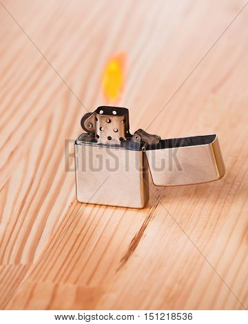 Cigarette lighter with fire on a natural light wooden table.