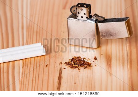 Cigarette lighter with cigarettes and tobacco on a light natural wooden table.