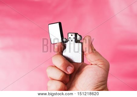 Hand of a man holding cigarette lighter against light pink background.