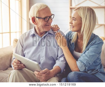 Handsome old man and beautiful young girl are using a digital tablet talking and smiling while sitting on couch at home