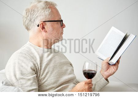 age, leisure and people concept - smiling senior man with wine glass reading book at home
