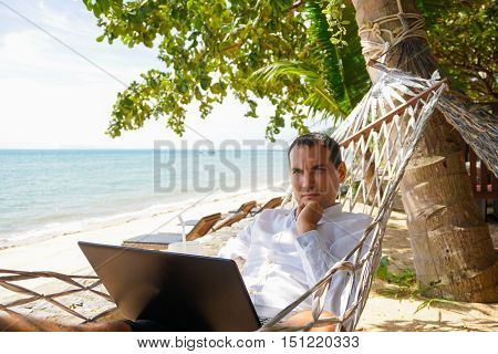 Serious man work on laptop in white shirt relaxing in hammock with seaview