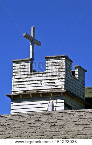 Peeling paint on the wood steeple and cross of an old church