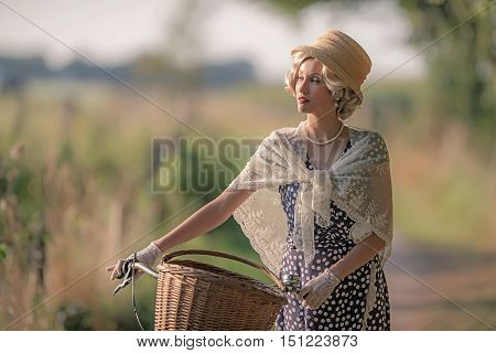 Retro Woman Dressed In 1930S Fashion Standing With Bicycle In Rural Landscape.