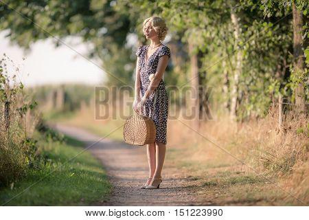 1920S Retro Fashion Woman Standing With Handbag On Rural Pathway.