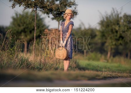 Vintage 1930S Summer Fashion Woman With Blue Dress And Straw Hat Standing With Handbag On Rural Road