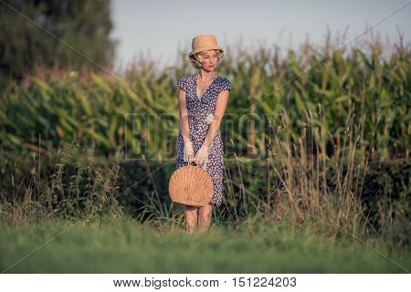 Vintage 1920S Summer Fashion Woman With Blue Dress And Straw Hat Standing With Handbag In Rural Land