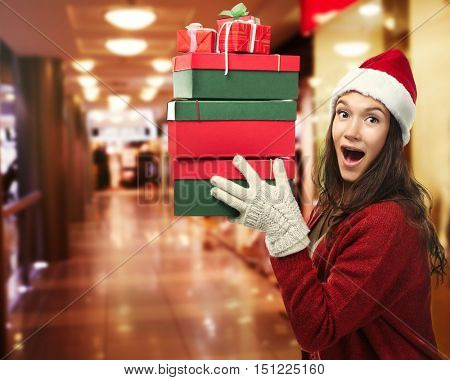 Beautiful happy woman with Christmas gifts on blurred market background. Christmas shopping concept.