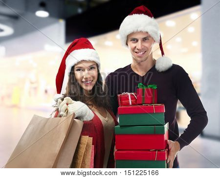 Young couple with Christmas purchases on blurred market background. Christmas shopping concept.