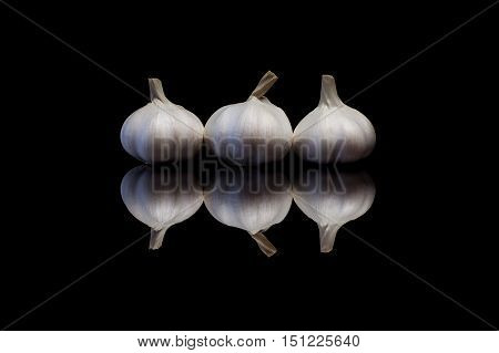 Three garlic isolated on a black reflective background