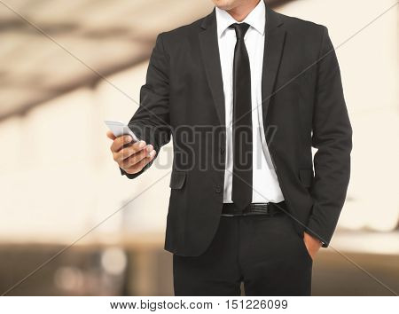 Businessman holding phone in hand on  blurred office background. Lawyer and notary concept.
