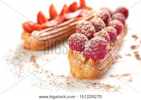 Delicious eclairs with berries, ground cinnamon and sugar powder on white surface