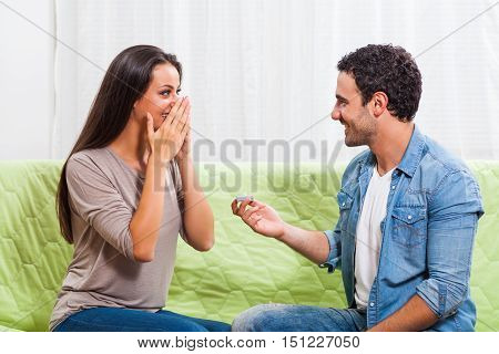 Young couple is sitting at sofa at home. Man is proposing to his woman.