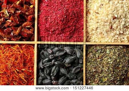 Different spices in wooden cells, closeup