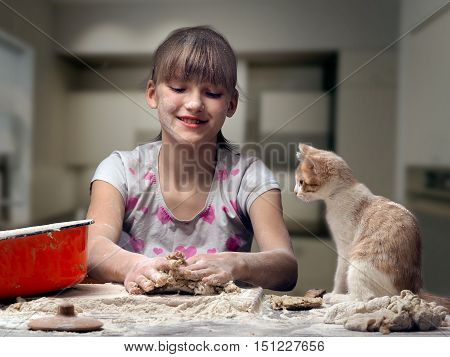 Funny girl kneads dough. kitten sitting next to. The girl a cat and a table - all in flour