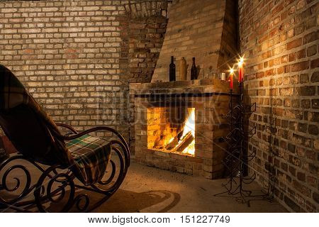 Rocking chair by the fireplace in brick room and candles