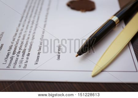 Pen, office knife and old notarial wax seal on document, closeup