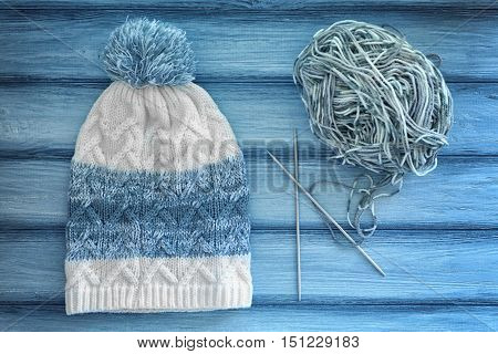 Knitted cap, ball of yarn and needles on wooden background