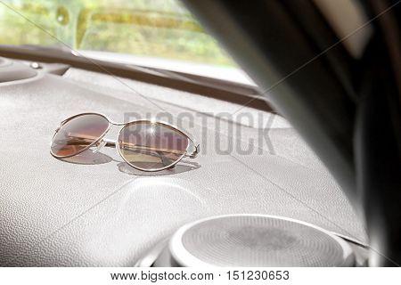 Sunglasses on car panel