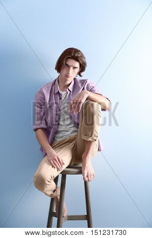 Handsome young man sitting on stool on blue background