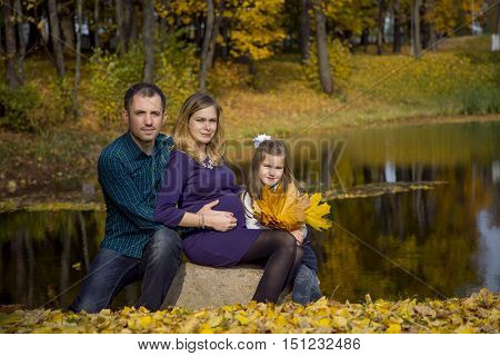 Happy pregnant family walking in autumn Park