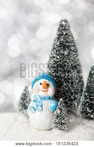 Snowman with lights in the background.