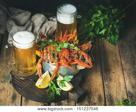 Two pints of wheat beer and boiled crayfish in metal pan served with with lemon and parsley on dark round serving board over rustic wooden background, selective focus, copy space