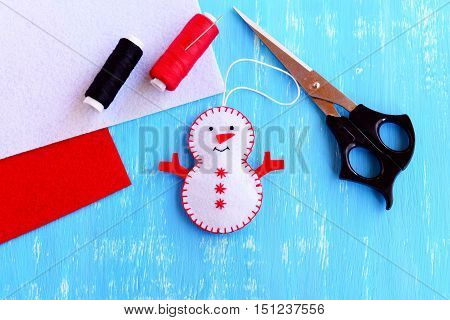 Christmas snowman ornament. Step. Felt Christmas snowman, scissors, thread, needle, felt pieces on wooden background. Easy handmade Christmas decoration. Sewing project. Top view