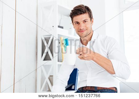 Smiling young businessman drinking cup of tea at lunch break in the office