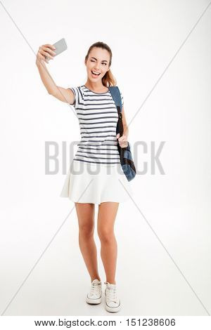 Happy woman student making selfie photo on smartphone and winking isolated on a white background