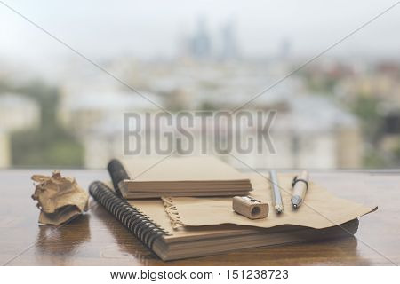 Closeup of two brown spiral notepads pen pencil sharpener and crumpled paper ball on blurry city background