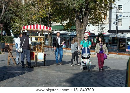 Traditional turkish Bakery Street mobile Vendor and Groups of Tourists from around the World walking. Istanbul, Turkey, November 18, 2015
